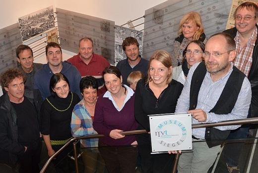 JEZT - Das Team der Stsedtischen Museen und ihr Direktor Dr Matias Mieth praesentieren das Museumssiegel des  Museumsverbands - Foto © Stadt Jena Glasser