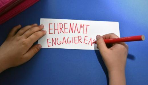 JEZT - Ein Schulkind schreibt die Worte Ehrenamt und engagieren auf ein Blatt Papier. - Symbolfoto © FSU Günther