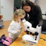 Frau Dr. Christina Walther (witelo e.V./ Schülerforschungswerkstatt) erklärt der 4jährigen Maja aus Jena das Stereomikroskop. - Foto © JenaWirtschaft