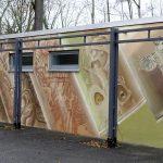 Eine Seite der neu gestalteten Toilettenanlage auf der Rasenmühleninsel. mit der Thematik Fallenden Spraydosen. - Foto © Stadt Jena Roswitha Putz